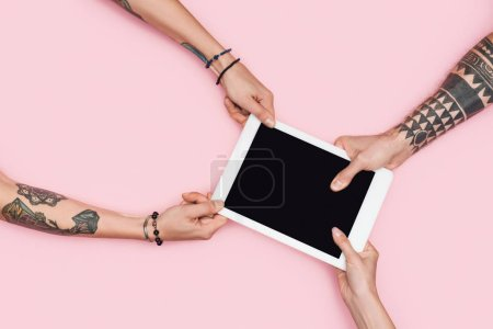 partial view of shopaholics pulling digital tablet with blank screen isolated on pink