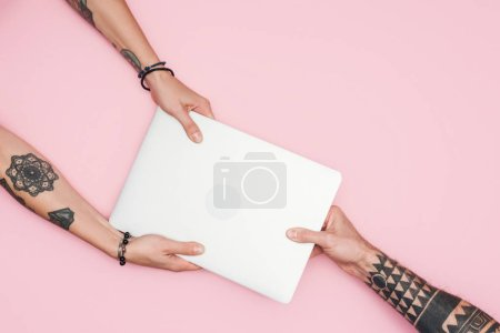 cropped view of tattooed people pulling laptop during sale isolated on pink
