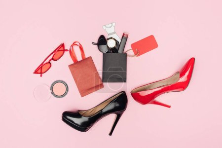 flat lay with high heels and little shopping bags with cosmetics and accessories isolated on pink