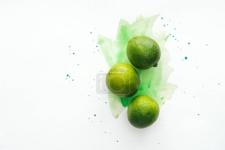 top view of whole three ripe limes on white surface with green watercolor