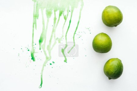 elevated view of whole limes on white surface with green watercolor