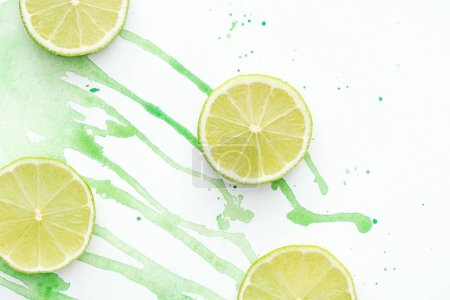 top view of cut limes on white surface with green watercolor