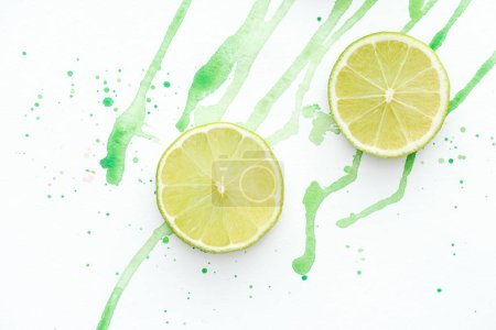 elevated view of two pieces of ripe limes on white surface with green watercolor