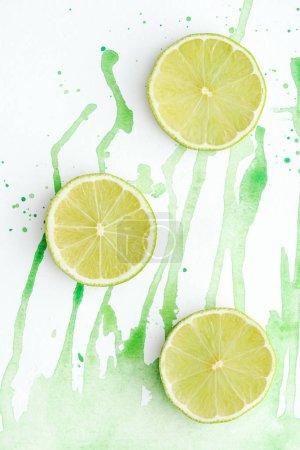 Photo pour Vue de trois pièces de limes mûrs sur une surface blanche avec vert aquarelle - image libre de droit