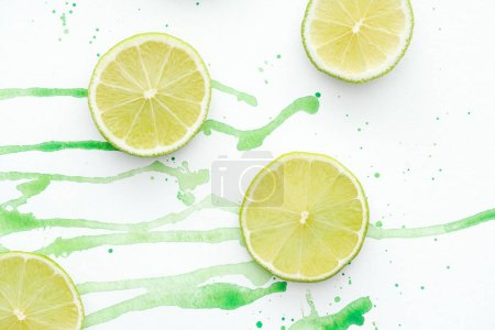 top view of pieces of cut ripe limes on white surface with green watercolor