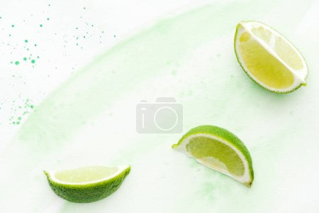 top view of pieces of yummy limes on white surface with green watercolor