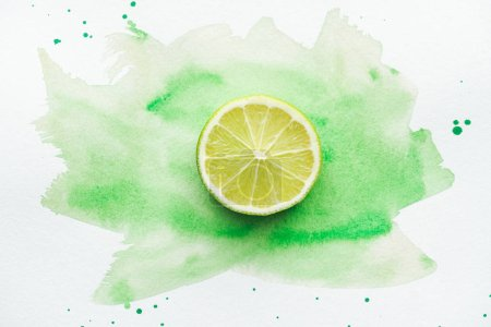 top view of piece of ripe citrus on white surface with green watercolor