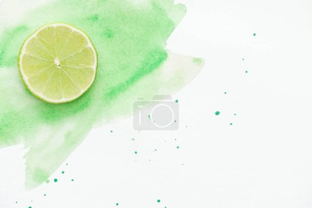 top view of piece of tasty lime on white surface with green watercolor