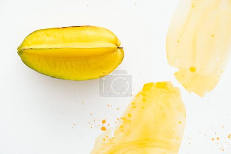 elevated view of exotic sweet carambola on white surface with yellow watercolor