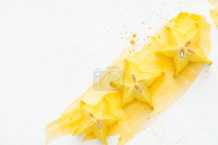 Foto de Vista superior de tres frutas exóticas de la estrella en la superficie blanca con acuarela amarilla - Imagen libre de derechos