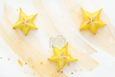 Photo for Elevated view of three sweet star fruits on white surface with yellow watercolor - Royalty Free Image