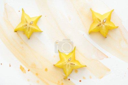 Photo pour Vue de trois fruits sucrés de star sur une surface blanche avec aquarelle jaune - image libre de droit