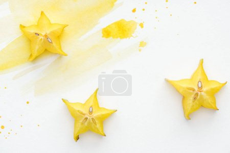 top view of three ripe star fruits on white surface with yellow watercolor