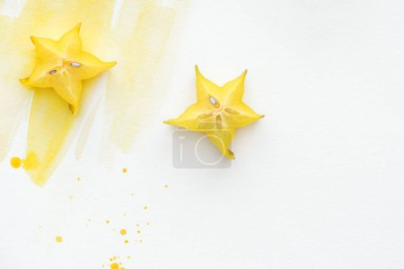 Photo for Top view of two sweet star fruits on white surface with yellow watercolor - Royalty Free Image
