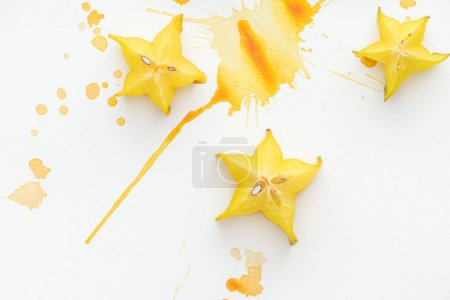 top view of three star fruits on white surface with yellow paint splashes