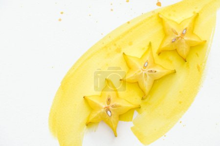 top view of exotic sweet star fruits on white surface with yellow watercolor