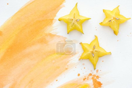 top view of star fruits on white surface with orange watercolor