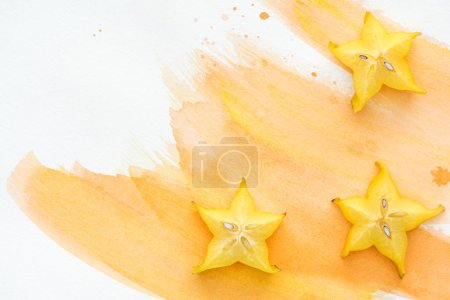 elevated view of tasty star fruits on white surface with orange watercolor