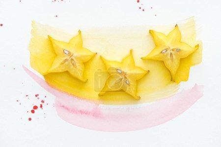 Draufsicht auf drei reife Sternfrüchte auf weißer Oberfläche mit gelben und rosa Aquarellen