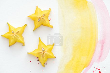 top view of three carambolas on white surface with yellow and pink watercolors