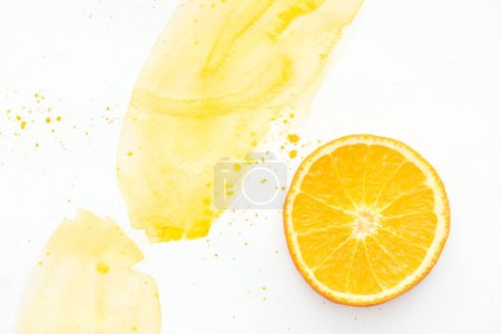 top view of yummy orange piece on white surface with yellow watercolor