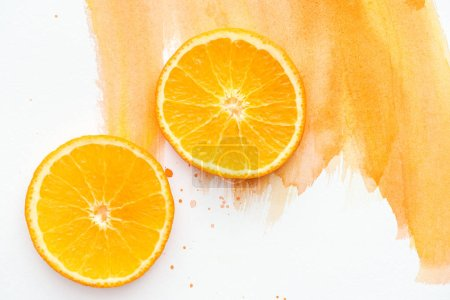top view of two ripe orange pieces on white surface with orange watercolor