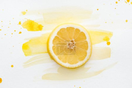 Photo for Elevated view of lemon piece on white surface with yellow watercolor - Royalty Free Image