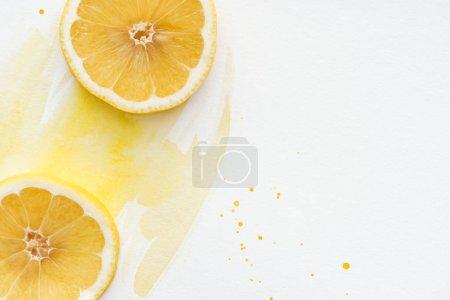 Photo pour Vue de dessus des morceaux de citron délicieux sur une surface blanche avec aquarelle jaune - image libre de droit