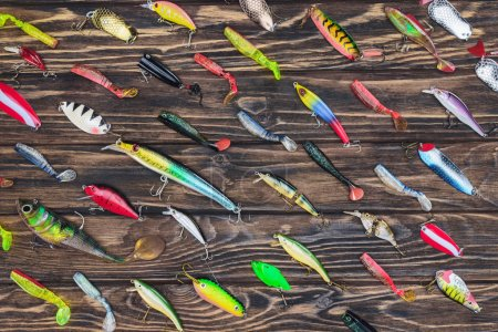 top view of arranged various fishing bait on wooden background