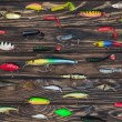 Flat lay with arranged various fishing bait on woo...
