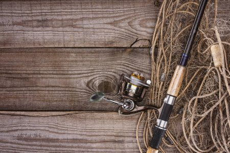 top view of fishing net and fishing rod on wooden planks