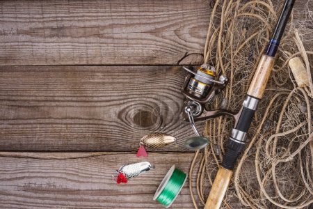 top view of reel, fishing rod, bait and fishing net on wooden background