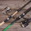 Top view of fishing rods on wooden background, min...
