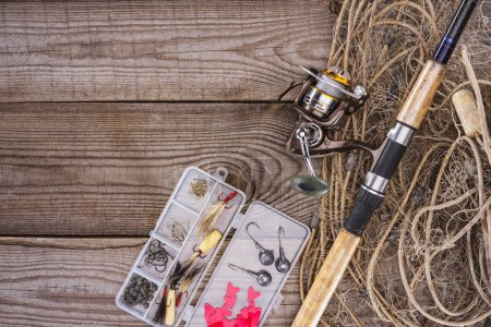 flat lay with fishing net, fishing rod and plastic box with fishing tackle and hooks on wooden planks