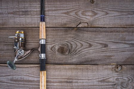 view from above of fishing rod on wooden planks, minimalistic concept