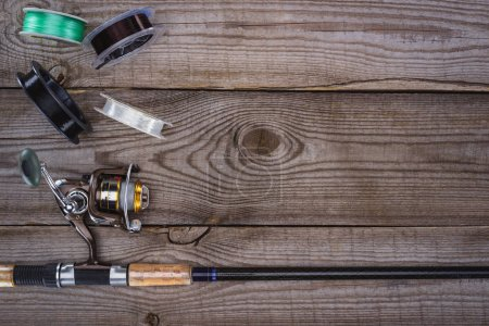 top view of various reels and fishing rod on wooden planks