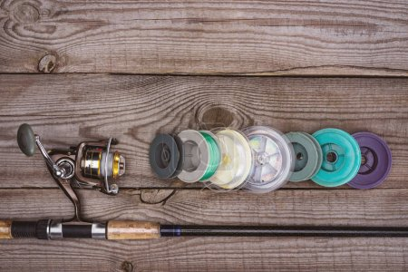 top view of fishing rod and various reels on wooden planks