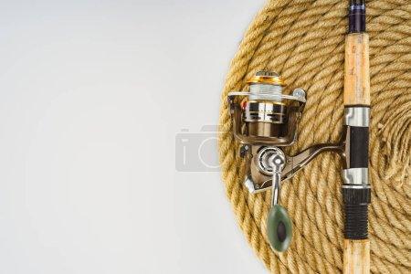 top view of fishing rod and nautical rope isolated on white, minimalistic concept