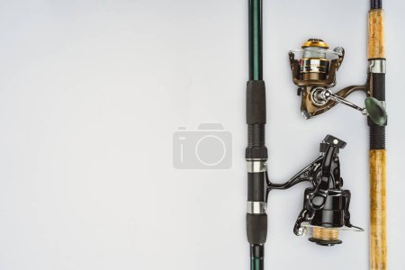 top view of two arranged fishing rods isolated on white, minimalistic concept