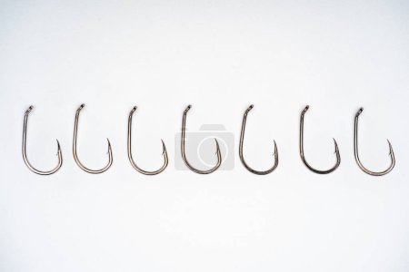 top view of fishing hooks placed in row isolated on white