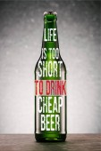beer bottle on tabletop on grey background with