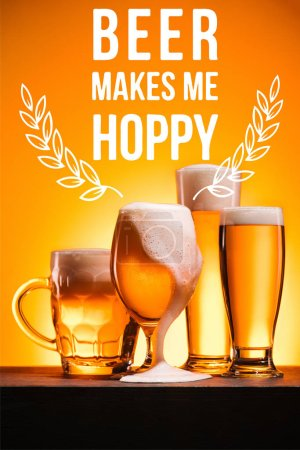 """Photo for Arranged mugs of cold beer with froth on orange background with """"beer makes me hoppy"""" inspiration - Royalty Free Image"""