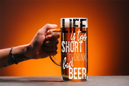 """Photo for Cropped shot of woman holding glass of cold beer with foam on orange backdrop with """"life is too short to drink cheap beer"""" inspiration - Royalty Free Image"""