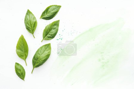 Photo for Top view of delicious basil leaves on white surface with green watercolor strokes - Royalty Free Image