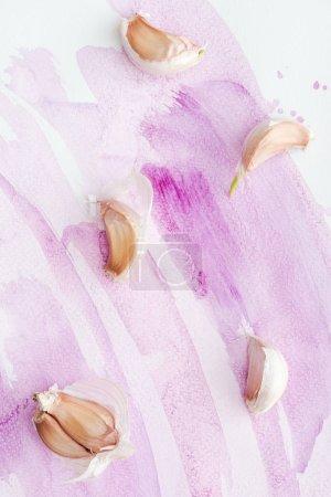 Foto de Vista superior de delicioso ajo crudo sobre la superficie blanca con trazos de acuarela rosa - Imagen libre de derechos