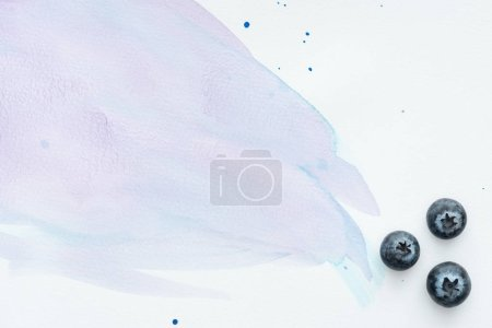 top view of juicy blueberries on white surface with purple watercolor strokes