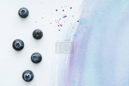 top view of delicious blueberries on white surface with purple watercolor strokes