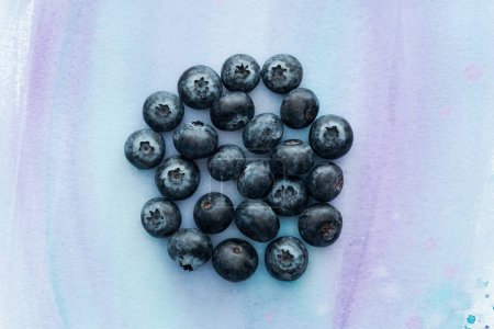 top view of heap of blueberries on white surface with purple watercolor strokes