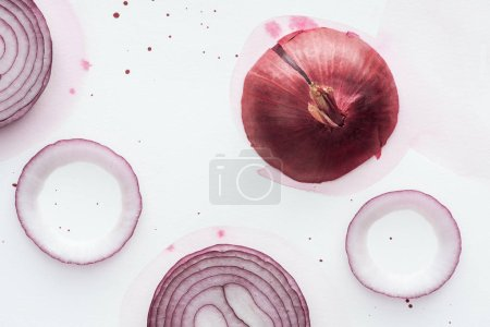 top view of raw whole red onion with rings on white surface with pink watercolor blots