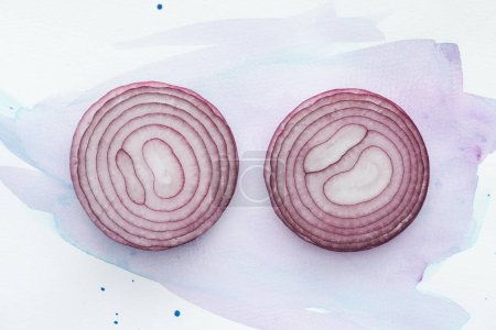top view of two slices of red onion on white surface with purple watercolor strokes